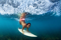 Underwater photo of surfer girl on surf board in ocean. Sportive girl in bikini in action. Surfer with surf board dive underwater under breaking ocean wave stock images