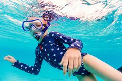 Little girl snorkeling. Underwater photo of young girl swimming and snorkeling in tropical ocean royalty free stock images