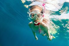 Little girl snorkeling. Underwater photo of young girl swimming and snorkeling in tropical ocean stock photo