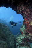 Underwater photography : Diver in cave. Female scuba diver in front of an underwater cave royalty free stock photo