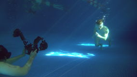 Underwater photography. A male model is posing underwater. A young handsome man is running along the bottom. Behined the. Scenes. Making of. 4K stock video footage
