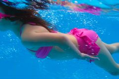 Underwater pink bikini little girl swimming Royalty Free Stock Photos