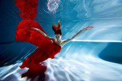 Underwater in the pool with the purest water. Beautiful young girl in a scarlet dress and flowing hair. Royalty Free Stock Image