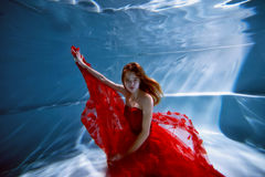 Underwater in the pool with the purest water. Beautiful young girl in a scarlet dress and flowing hair. royalty free stock photography