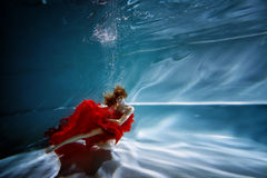 Underwater in the pool with the purest water. Beautiful young girl in a scarlet dress and flowing hair. Royalty Free Stock Photo