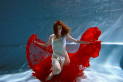 Underwater in the pool with the purest water. Beautiful young girl in a scarlet dress and flowing hair. Royalty Free Stock Photos