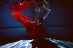Underwater in the pool with the purest water. Beautiful young girl in a scarlet dress and flowing hair. Stock Photography