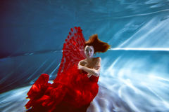 Underwater in the pool with the purest water. Beautiful young girl in a scarlet dress and flowing hair. Royalty Free Stock Images