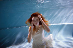 Underwater in the pool with the purest water. Beautiful young girl in a scarlet dress and flowing hair. Stock Image