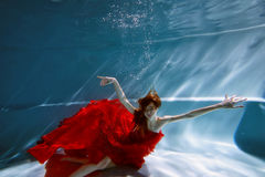 Underwater in the pool with the purest water. Beautiful young girl in a scarlet dress and flowing hair. Underwater in the pool with the purest water. Beautiful Royalty Free Stock Photo
