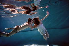 Underwater in the pool with the purest water. Loving couple hugging. The feeling of love and closeness Stock Photo