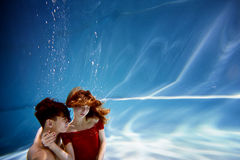 Underwater in the pool with the purest water. Loving couple hugging. The feeling of love and closeness. Soft focus. Underwater in the pool with the purest water Royalty Free Stock Image