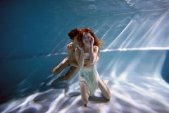 Underwater in the pool with the purest water. Loving couple hugging. The feeling of love and closeness. Soft focus. Underwater in the pool with the purest water stock image