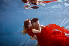 Underwater in the pool with the purest water. Loving couple hugging. The feeling of love and closeness. Soft focus. Underwater in the pool with the purest water royalty free stock photos