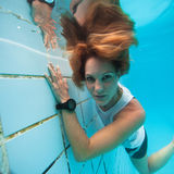 Underwater in a pool. Woman freediving underwater in a pool Stock Photo