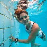 Underwater in a pool. Woman freediving underwater in a pool Royalty Free Stock Image