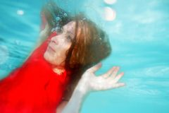 Underwater portrait of young beautiful woman. In red dress Royalty Free Stock Photo