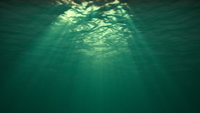 Underwater Reflection in the Ocean. Blue version, water ripples coming towards camera. With tiny particles in the water. Sun rays shinning down. Seamless looping stock video footage
