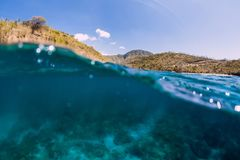 Underwater scene with clear ocean water and mountains stock image
