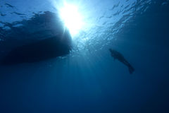 Underwater scene : scuba diver in deep water. A scuba diver in deep blue water with a dive-boat above and sunbeams in the background stock photos