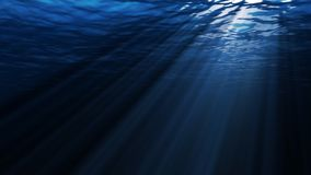 Underwater scene with sunrays shining through the water`s surface. Looping stock video