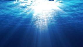 Underwater scene with sunrays shining through the water`s surface. Looping stock video footage