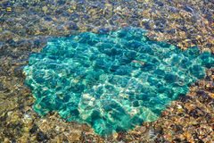 Underwater sea stones, surface with ripples and waves, beautiful pattern transparent clear water.  stock photography