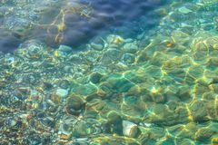 Underwater sea stones, surface with ripples and waves, beautiful pattern transparent clear water.  stock images