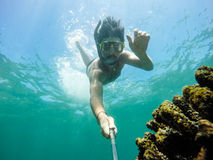 Underwater selfie shot with selfie stick. Royalty Free Stock Photography