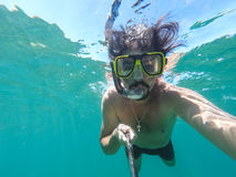Underwater selfie shot with selfie stick. Royalty Free Stock Image