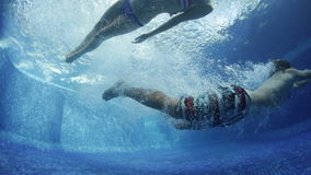 Underwater shoot of the couple in the pool. Underwater shoot of the couple jumping in the pool stock footage