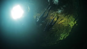 Underwater shoot of couple swimming on the water surface. Underwater shoot of couple swimming inside the underwater cave. High level of noise, iso 800 stock video footage