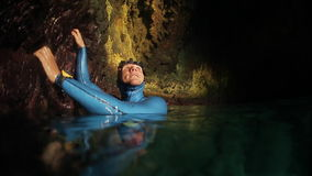 Underwater shoot of freediver. Freediver in wetsuit explores the underwater cave. High level of noise, iso 800 stock video