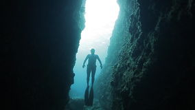 Underwater shoot of freedivers. Swimming in the underwater narrow canyon stock footage