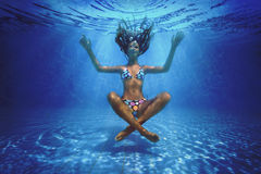 Underwater shoot. Of a relaxed smiling woman flying in a swimming pool in lotus position Royalty Free Stock Photos