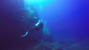 Underwater shoot of a scuba divers swimming in blue clear water. stock video footage