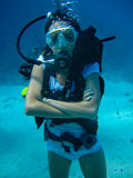 Underwater shoot of a woman diving with scuba. And looking at the camera stock photos