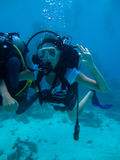 Underwater shoot of a woman diving and showing ok signal. Underwater shoot of a woman diving with scuba and showing ok signal royalty free stock image