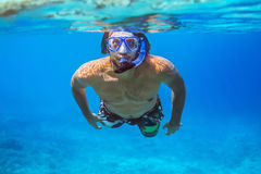 Underwater shoot of a young man snorkeling in a tropical sea. Vacation concept Royalty Free Stock Photo