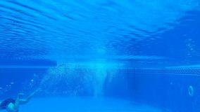 Underwater shooting as a man dives into the pool and swims under the water. Slow motion stock video footage