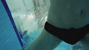 Underwater - man dives in swimming pool. Underwater shooting. Young active sportsman makes run-up and jumps into the water of the pool. Young swimmer trains and stock footage