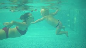 An underwater shot of cute blonde toddler swimming under the water together with his mother in the swimming pool. Then. His mother is lifting him from the water stock footage