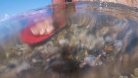 Underwater shot of feet walking on sandy ocean beach. The camera moves under the water stock video footage