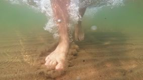 Underwater shot of feet walking on sandy ocean beach. The camera moves under the water stock video