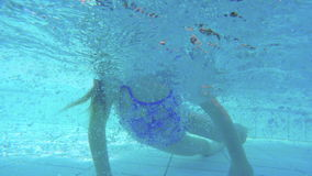 Underwater shot of little girl diving in a swimming pool stock footage