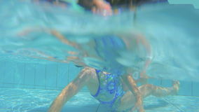 Underwater shot of little girl diving in a swimming pool. Slow motion Underwater shot of a little girl diving in a swimming pool stock video