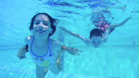 Underwater shot of two kids diving in a swimming pool