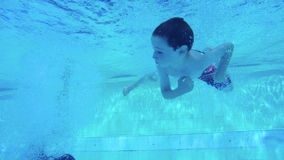 Underwater shot of two kids diving in a swimming pool. Slow motion Underwater shot of two kids diving in a swimming pool stock footage
