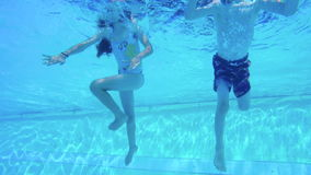 Underwater shot of two kids diving in a swimming pool stock video footage