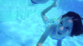 Underwater shot of two kids diving in a swimming pool stock footage
